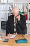 Young businessman with bald head is calling Stock Photography