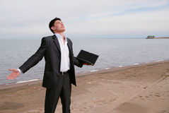 Young businessman on the beach Stock Images