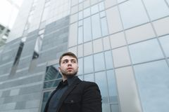 Businessman with a beard and a black suit stands on the background of modern light architecture Stock Photos