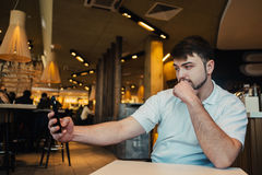Young businessman with a beard makes a nice restaurant selfie. Young businessman with a beard makes selfie in a beautiful and cozy restaurant Stock Images