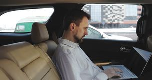 Young businessman with a beard uses a touchpad on a laptop on backseat of car. A rich man in a shirt works at the computer in the car. Business concept stock footage