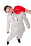 Young businessman being hit with a boxing glove. Isolated on a white background Stock Photos
