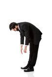 Young businessman bending down. Stock Photo