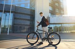 Young businessman with bicycle and smartphone on city street. Royalty Free Stock Image