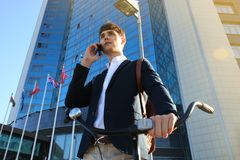 Young businessman with bicycle and smartphone on city street. Royalty Free Stock Photography