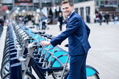 Young businessman with a bicycle. Smiling businessman take his bicycle from parking Stock Images