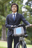 Young businessman with bicycle standing at park Royalty Free Stock Photo