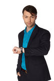 Young businessman black suit casual poses. Young businessman black suit looking at his watch at studio Stock Image