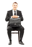 Young businessman in black suit holding a briefcase and waiting Royalty Free Stock Photo