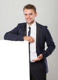 Young businessman in black suit leaning on blank white sign Stock Photo