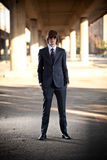 Young businessman in black suit posing against city landscape Stock Photo