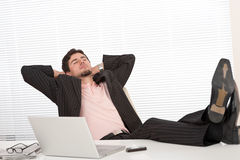 Young businessman in black suit relaxing at office Royalty Free Stock Photos