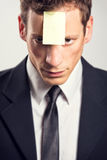 Young businessman with blank note on his forehead Royalty Free Stock Photos