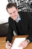 Young businessman with a blank paper sitting down Stock Image