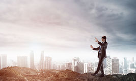 Young businessman in blindfold walking carefully and cityscape at background Stock Photography