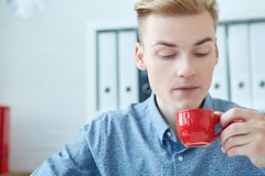Young businessman blowing a hot cup of coffee in office. Business or education pause, coffee house or tea shop concept. Stock Photography