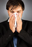 Young businessman blowing nose Royalty Free Stock Photos