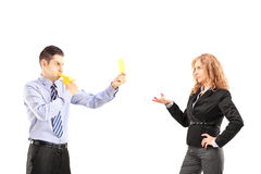 Young businessman blowing a wistle and showing a yellow card to Stock Photography