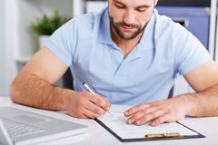 Young businessman in blue polo shirt signs a contract Royalty Free Stock Photos