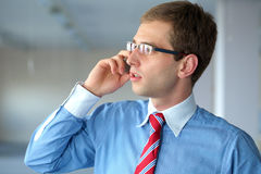 Young businessman in blue shirt talks over mobile Stock Photography