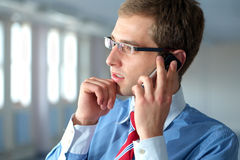Young businessman in blue shirt talks over mobile Royalty Free Stock Photo