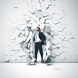 Young businessman breaking trough a wall Stock Photography