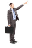 Young businessman with briefcase pointing in a direction Stock Images