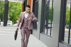 Hurrying to work. Full length of young businessman looking forward while running along the street Royalty Free Stock Photography