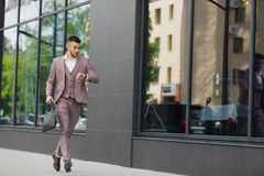 Young businessman with a briefcase running in a city street on a background of wall Stock Photo