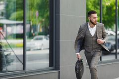 Hurrying to work. Full length of young businessman looking forward while running along the street Royalty Free Stock Photos