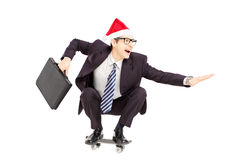 Young businessman with briefcase and santa hat riding a skateboa Stock Photos