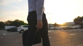 Young businessman with a briefcase walking in auto parking at sunrice time. Business man commuting to work. Confident. Guy in being on his way to office at stock video footage