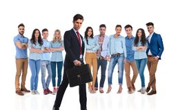 Young businessman with briefcase walking in front of his team. Young businessman with briefcase walking in front of his young team on white background while they royalty free stock photos