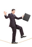 Young businessman with briefcase walking on a rope Royalty Free Stock Image