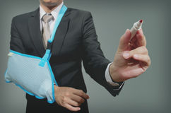 Young businessman with broken hand wearing an arm brace Royalty Free Stock Photos