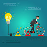 Young businessman or broker riding bicycle on a dynamo generator Royalty Free Stock Images