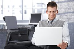 Young businessman browsing internet smiling Stock Image