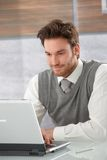 Young businessman browsing internet smiling. Young goodlooking casual office worker browsing internet on laptop, smiling stock photography