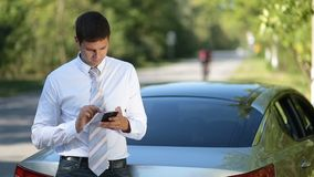 Young businessman browsing net with phone outdoors stock footage