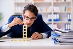 The young businessman building domino tower in office Royalty Free Stock Photo