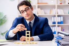 The young businessman building domino tower in office stock image