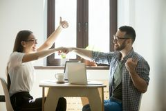 Business partners fist bumping after success good deal. Young businessman and businesswoman celebrating well done job. Employees fist bumping and showing thumb Royalty Free Stock Photography