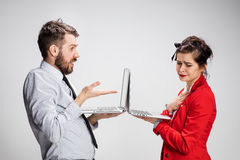 The young businessman and businesswoman with laptops communicating on gray background Stock Photos