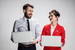 The young businessman and businesswoman with laptops communicating on gray background Stock Photography