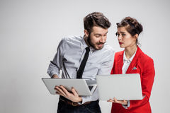 The young businessman and businesswoman with laptops communicating on gray background Stock Photo