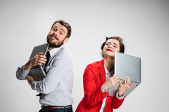 The young businessman and businesswoman with laptops on gray background Royalty Free Stock Photos