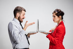 The young businessman and businesswoman with laptops on gray background Royalty Free Stock Photo