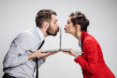 The young businessman and businesswoman with laptops kissing screens on gray background. Love on the Internet. The young businessman and businesswoman with Royalty Free Stock Image
