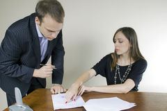 Young businessman and businesswoman signing Stock Photos