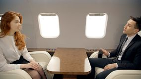 Young businessman and businesswoman are talking, sitting in airplane interior during flight. Young businessman and businesswoman are talking, sitting in stock footage